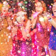 Happy friends making party throwing confetti – Young people celebrating on weekend night – Entertainment, fun, new year's eve, nightlife and fest concept – Focus on red hair girl hands